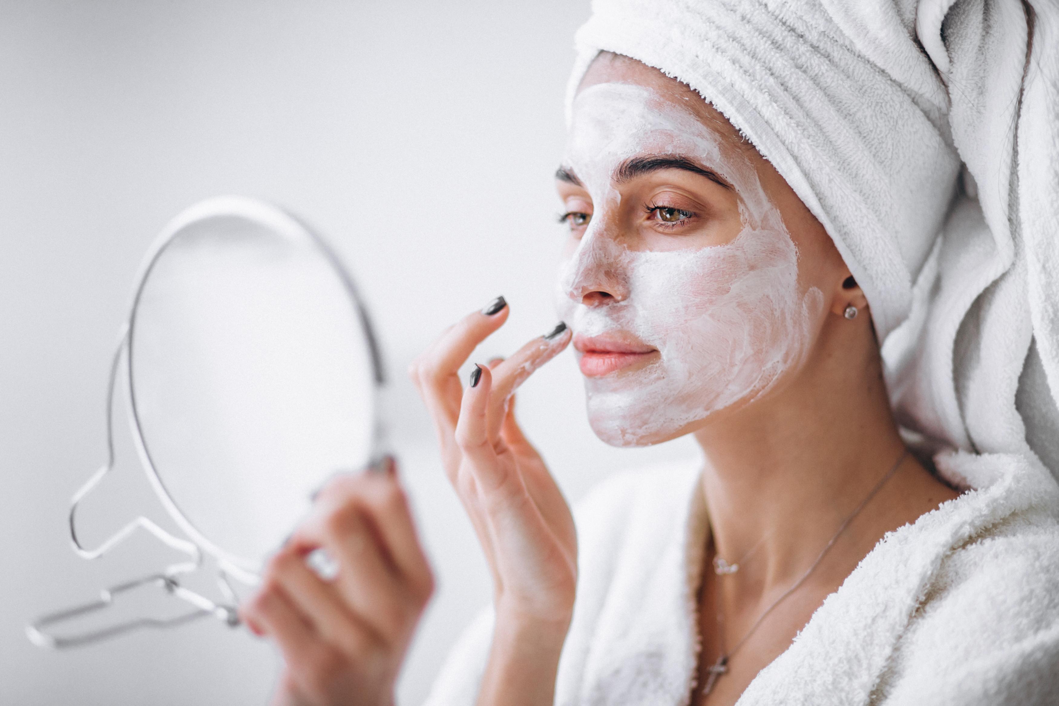 Woman aplying beauty mask,close up