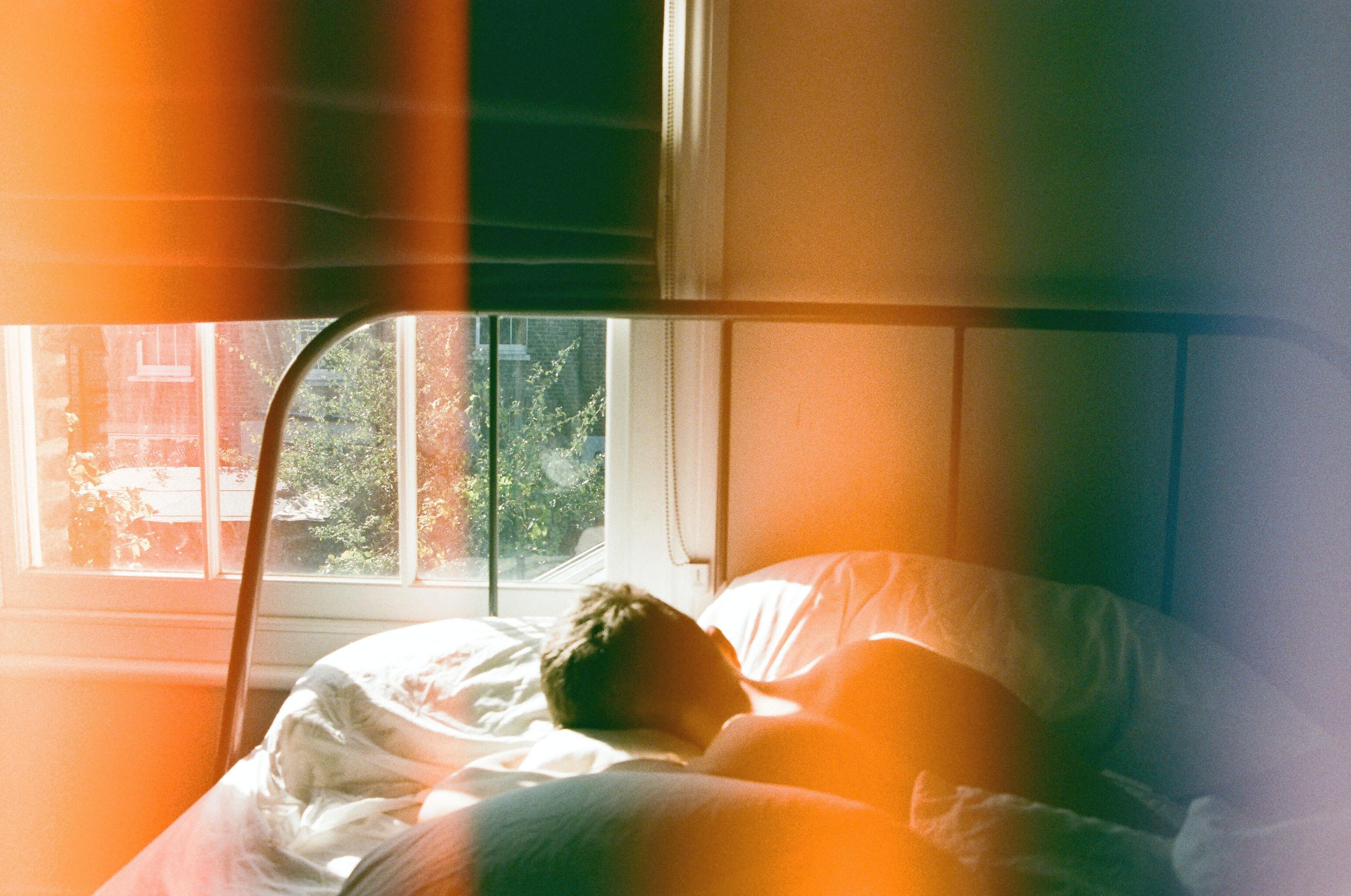 person-lying-in-bed-beside-window-1572728